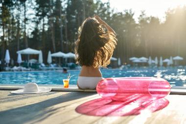 Frau sitzt am Rand eines Pools mit einem Cocktail