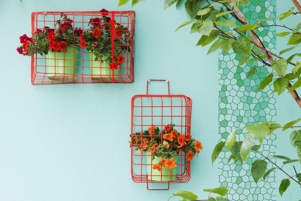 Blumen hängen in Fahrradkörben an der Wand als Blumendeko