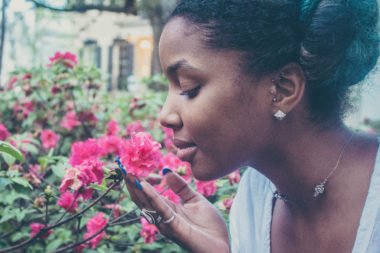 Frau riecht an pinker Blume.