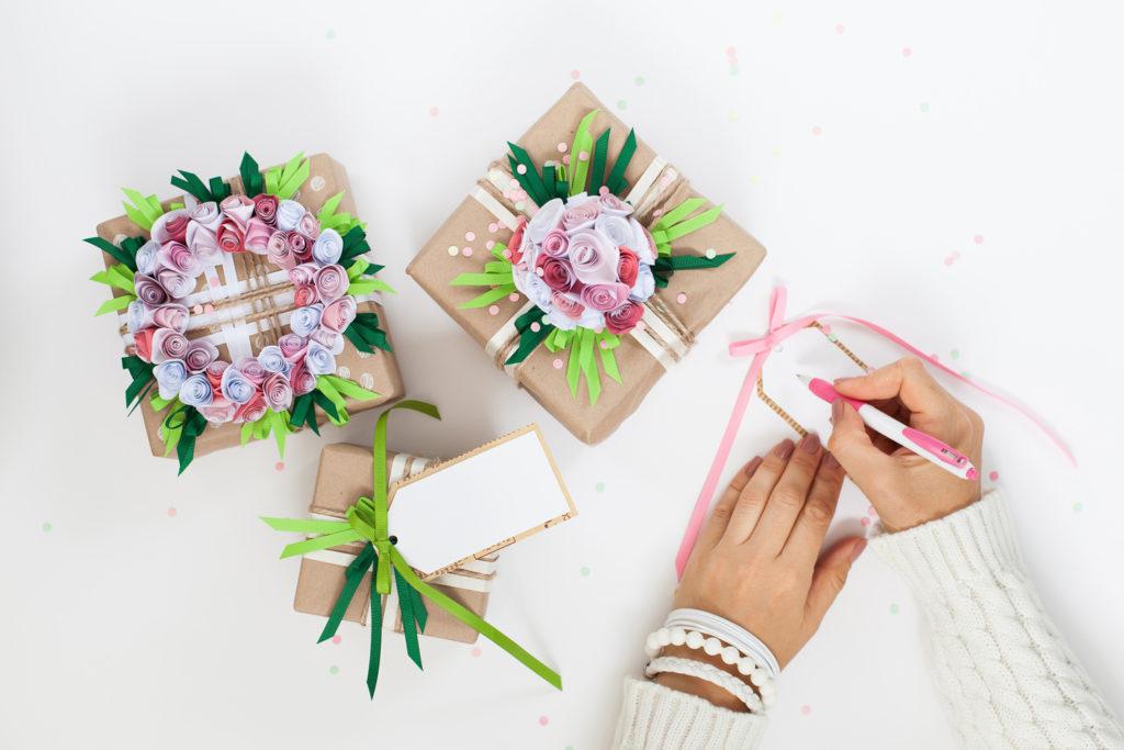 Geschenke verpacken und mit Bluemen dekorieren.
