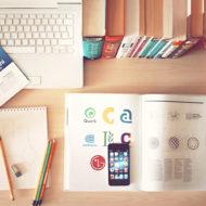 Geordneter Schreibtisch mit Büchern und Laptop.