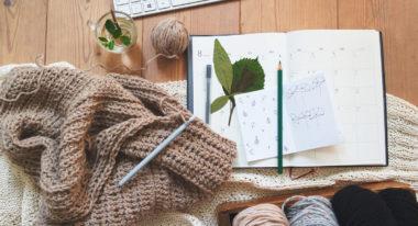 Wolle, Häkelnadel, Blätter und ein Notizbuch auf einem Holztisch