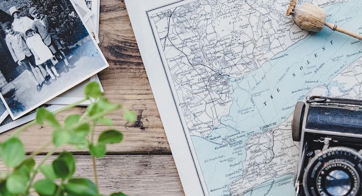 Kamera und Fotos liegen auf einem Tisch mit einer Landkarte