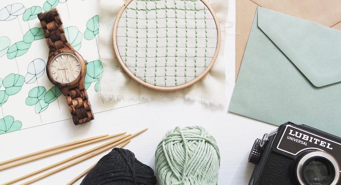 Stricknadeln, Wolle, Stickrahmen und eine Uhr liegen auf dem Tisch