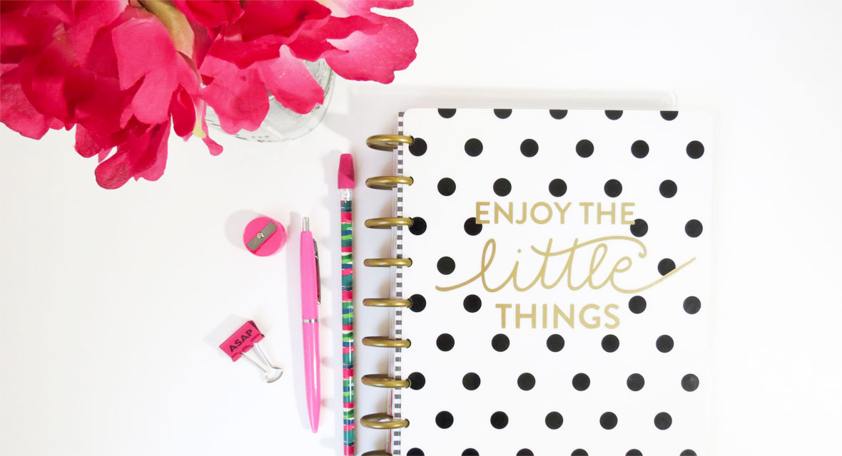 Ein Notizbuch und Stifte liegen neben Blumen auf dem Tisch