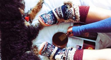 Eine Frau mit Socken sitzt mit ihrem Hund auf dem Bett