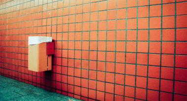 Ein Mülleimer hängt an einer orangefarbenen Wand