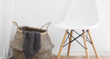 Weißer Eames Chair steht neben einem Wäschekorb