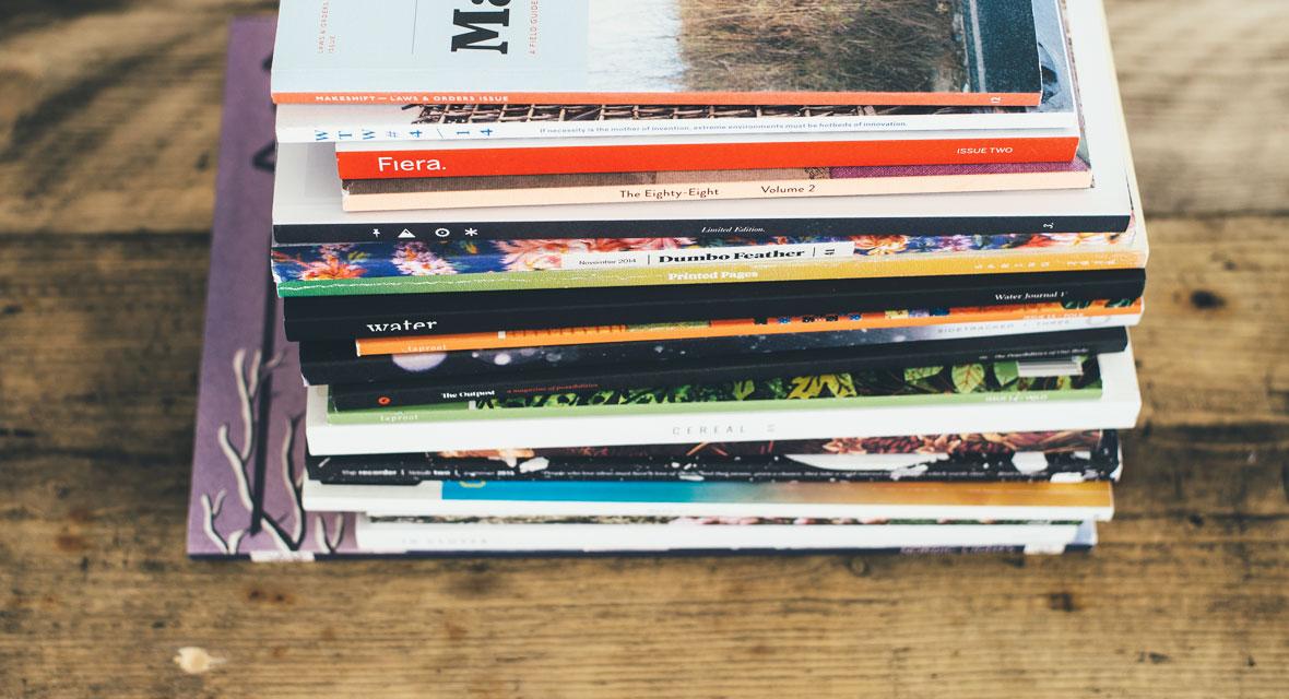 Zeitschriften liegen auf einem Holztisch