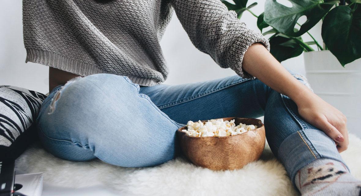 Frau sitzt in Jeans mit Popcorn auf dem Boden