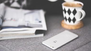 Smartphone, Zeitschriften und eine Tasse Kaffee auf einer Couch