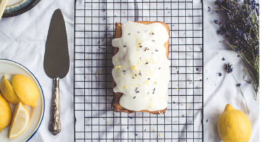 Ein Kuchen steht auf einem Gitter und Zitronen liegen außenherum