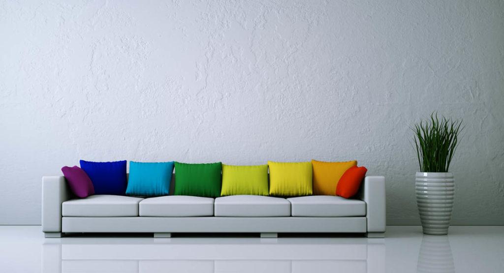 Mit Sofakissen in Regenbogenfarben werden aus kühlen Zimmern lebendige Räume.