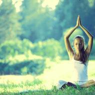 Frau macht Yoga Übungen im Park