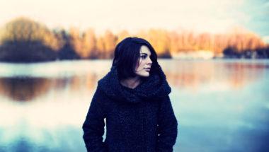 Frau steht alleine im Winter bei einem See