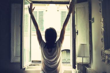 Frau steht mit gereckten Armen am Fenster