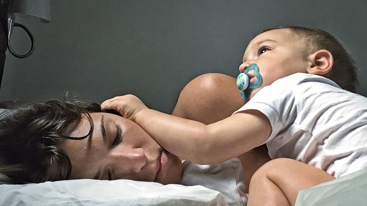 Baby liegt auf seiner schlafenden Mutter