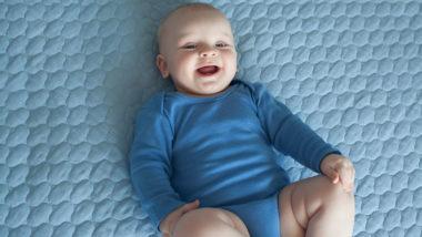 Baby liegt auf dem Rücken und lacht