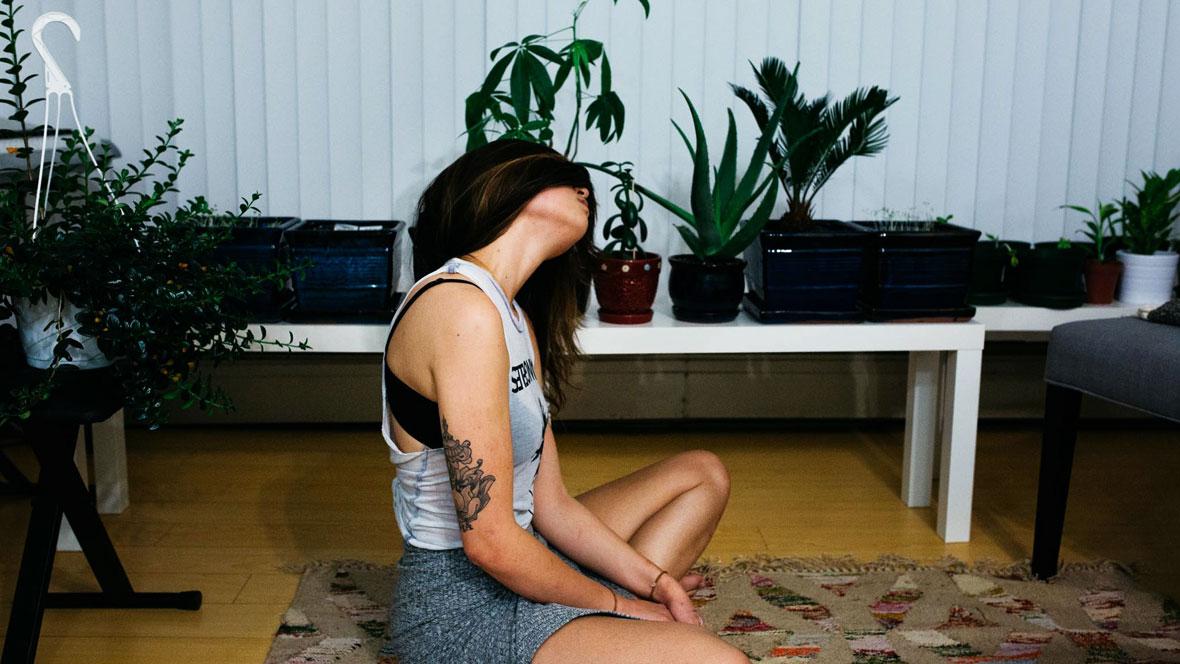 Frau sitzt im Wohnzimmer im Schneidersitz