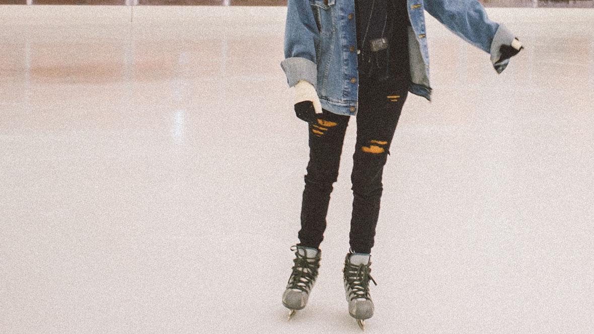 Mädchen in Jeansjacke läuft mit Schlittschuhen über das Eis