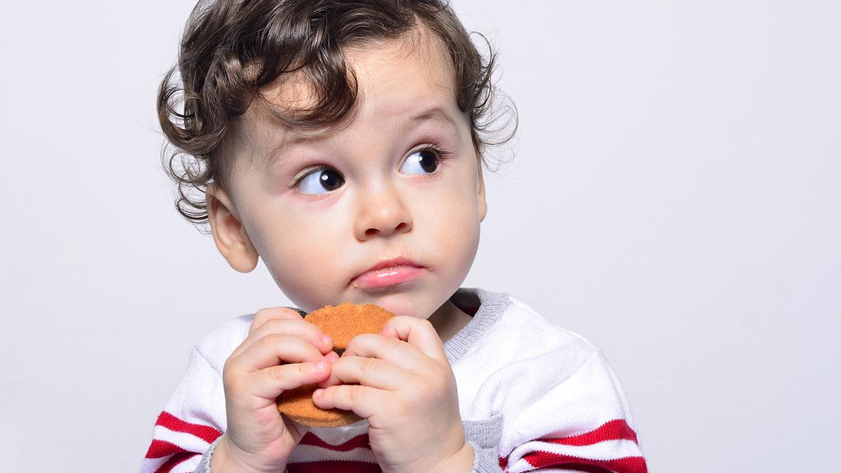 Junge sitzt im Hochstuhl ist isst einen Keks