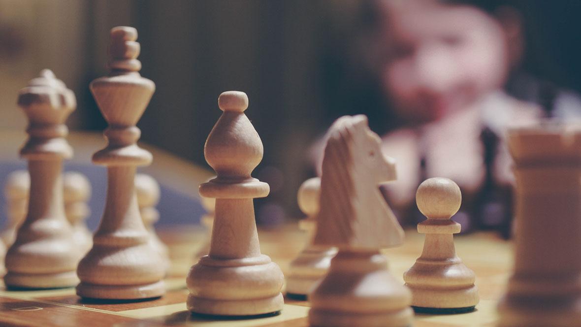 Schachbrett mit Figuren und einem Kind im Hintergrund