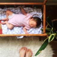 Baby liegt im Bett während es seine Mutter beobachter