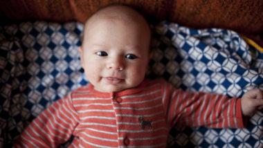 Baby liegt in seinem Bettchen und lächelt