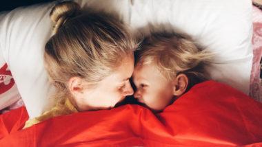 Mutter und Kind liegen im Bett und sehen sich in die Augen