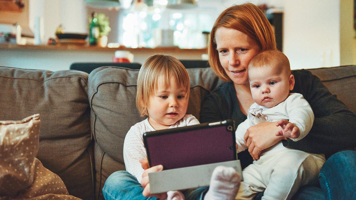 Mutter sitzt mit ihren zwei Kinder auf einem Sofa und zeigt ihnen was auf dem iPad