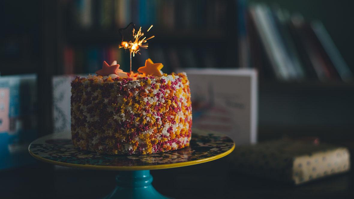 Bunter Kuchen für einen Kindergeburtstag mit einer Wunderkerze