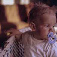 Baby steht in seinem Bett mit Schnuller im Mund