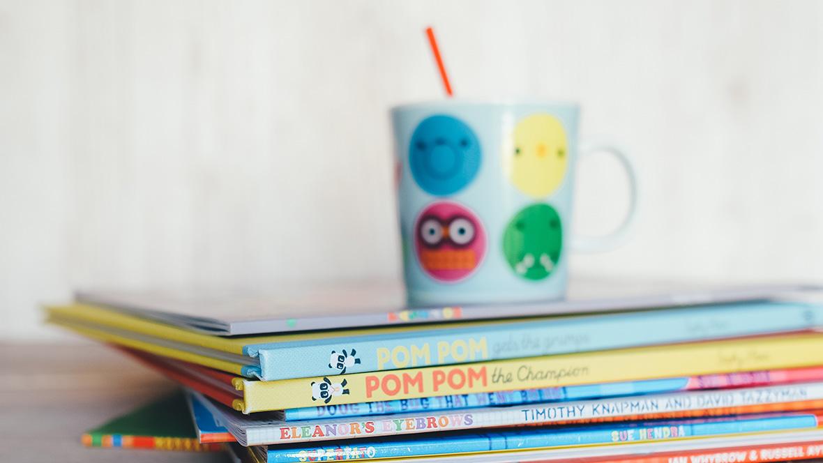 Eine Tasse steht auf einem Stapel Kinderbücher