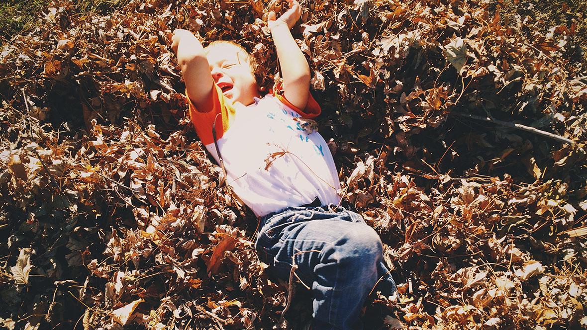 Junge liegt schreiend in einem Blätterhaufen