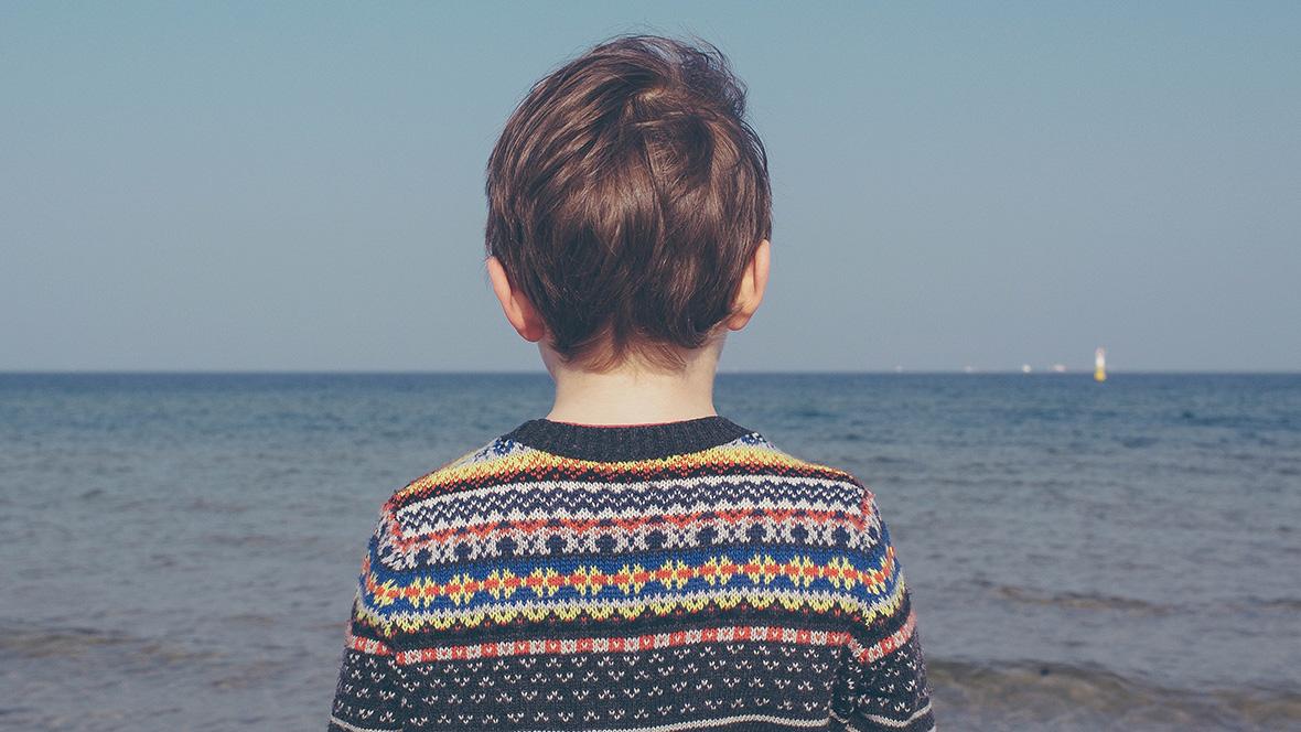 Junge mit Pullover starrt aufs Meer
