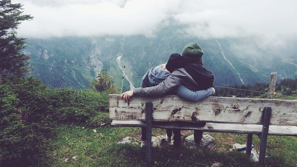 Ein Paar sitzt auf einer Bank in den Bergen