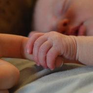 Baby liegt im Bett und umfasst den Finger der Mutter