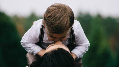 Mutter küsst ihren kleinen Sohn im Regen auf den Mund