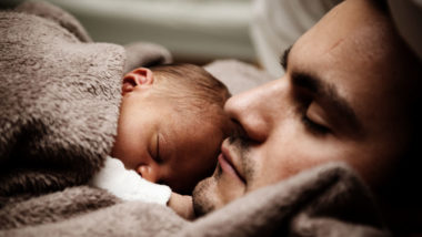 Baby schläft auf dem Arm von Papa