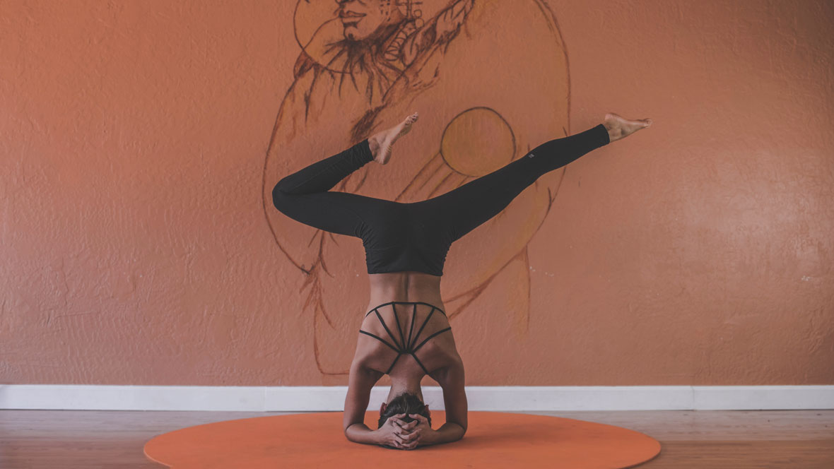 Frau macht eine Yogaübung vor einer Wand