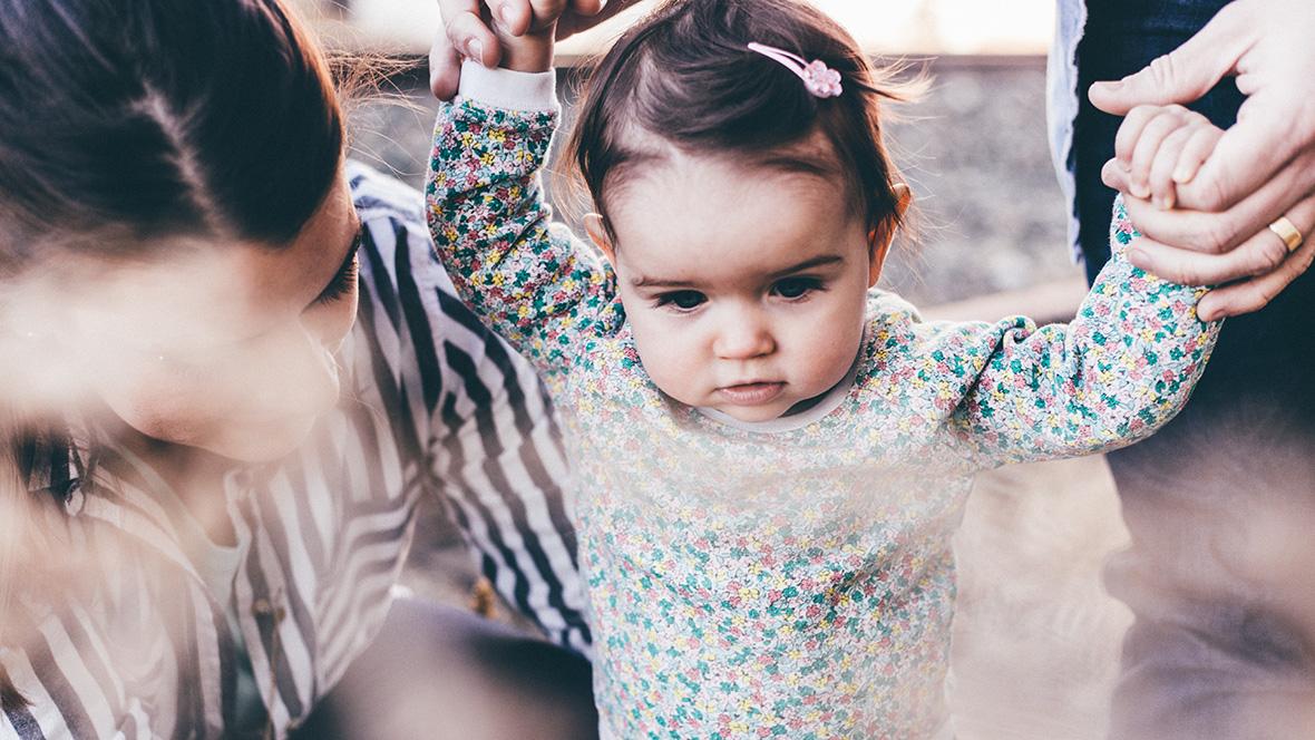 Ein kleines Mädchen wird von ihren Eltern an den Händen gehalten, um laufen zu lernen