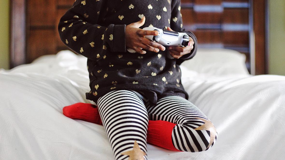 Ein Mädchen sitzt auf eine Bettkante und spielt Videospiele