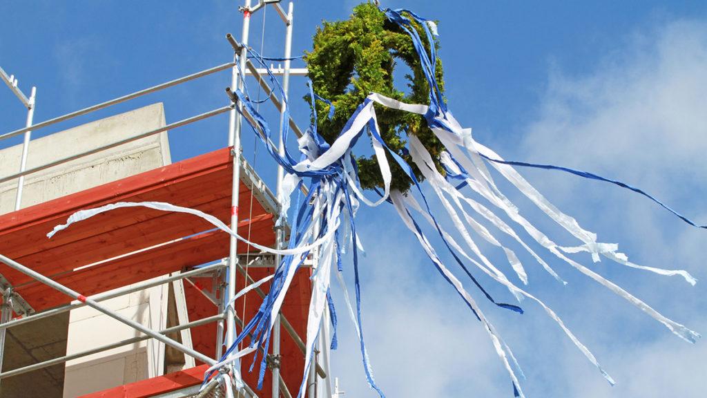 Beim Richtfest wird auf den Abschluss der bisherigen Arbeiten und Glück im neuen Heim angestoßen.