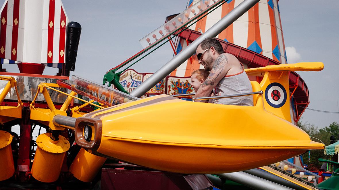Vater und Kind fahren Karussell auf dem Rummelplatz
