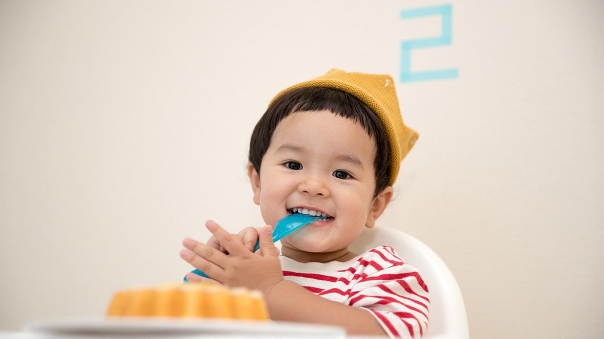 Ein kleiner Junge sitzt in einem Hochstuhl mit seinem Geburtstagskuchen vor ihm
