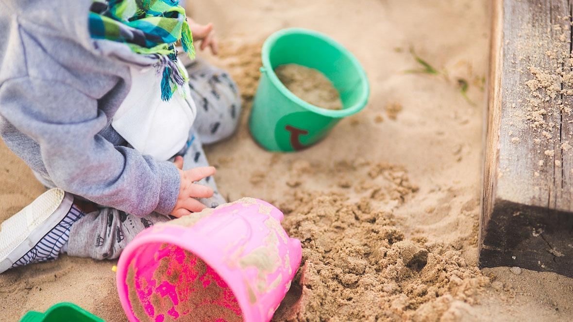 Kind spielt mit Förmchen im Sandkasten