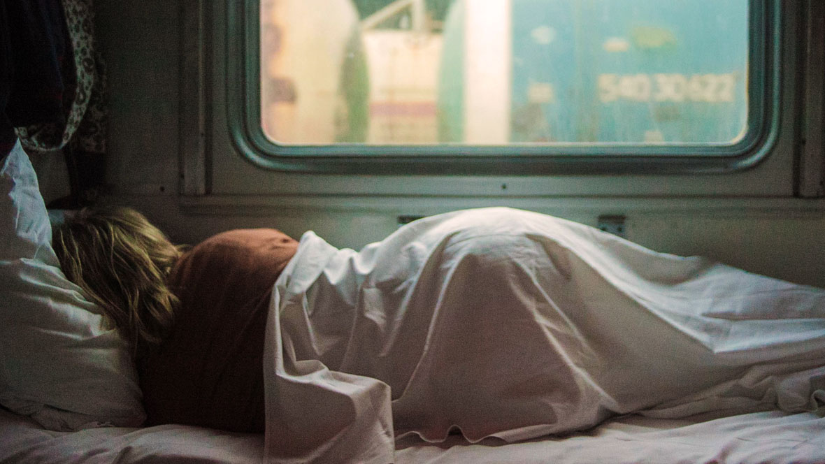 Eine Frau liegt in einem Wohnwagen und schläft