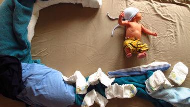 Baby liegt auf einem Bett voller Windeln