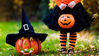 Mädchen im Halloweenkostüm steht neben einem Kürbis