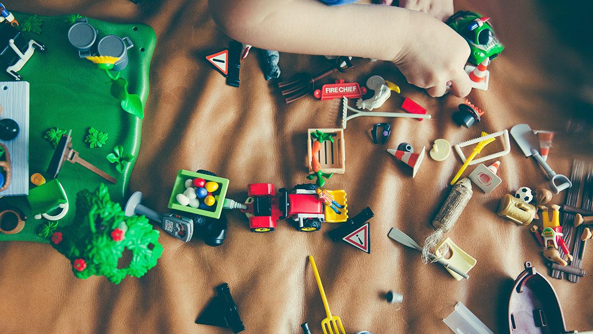 Kind spielt mit Playmobil auf der Couch